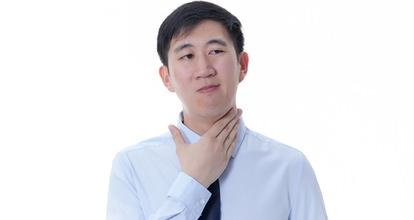 喉に手を当てる男性